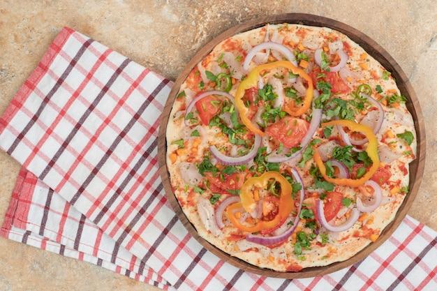 Pane pita rotondo con peperoni e cipolla sul piatto di legno.