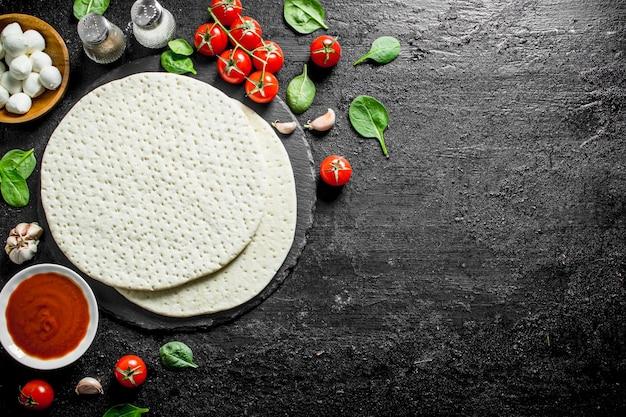 Круглое тесто для пиццы с моцареллой, томатной пастой и шпинатом. на черном деревенском фоне