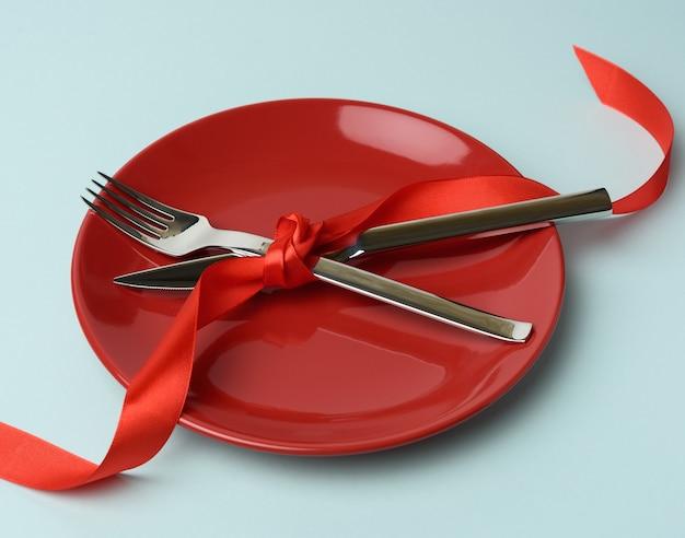 Круглая тарелка, металлическая вилка и нож, перевязанные красной шелковой лентой