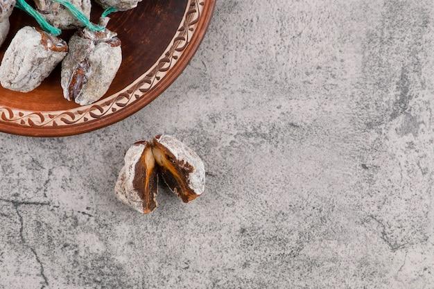 Un piatto rotondo pieno di frutti di cachi essiccati posto su un tavolo di pietra.