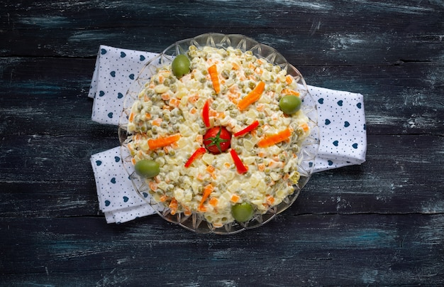 Round plate of russian salad with mayonnaise and vegetables