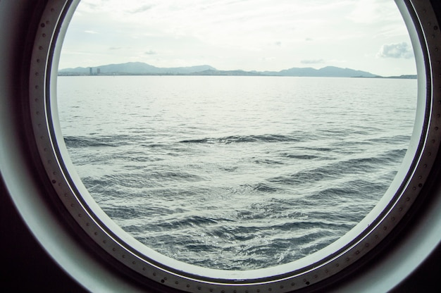 Круглый иллюминатор на круизном судне, внутренний вид через окно на побережье и море, восход солнца на море, крупный план