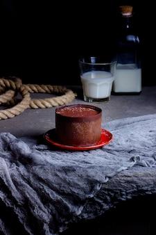 Круглое порционное итальянское тирамису, окруженное слоем шоколада