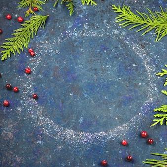 コピースペースとクランベリーとクリスマスツリーの枝を持つ丸い粉砂糖リング。