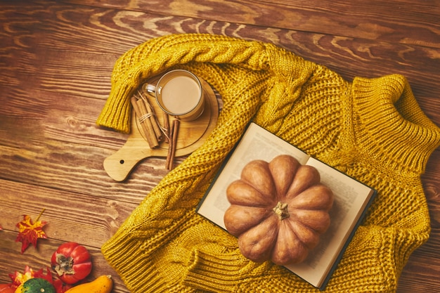 Round pumpkin vintage book cocoa and warm knitted sweater on wooden background hot coffee with cinna...