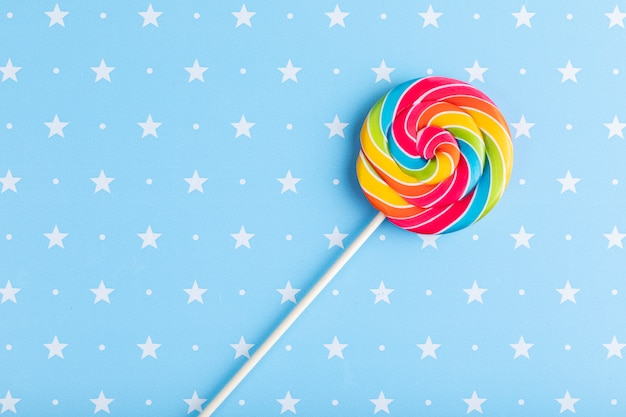 Round rainbow multicolor lollipop isolated on a blue with stars background. christmas, winter, new year or birthday concept.