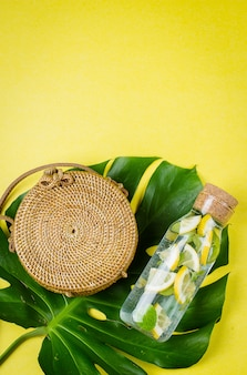 Round rattan bag and glass bottle with lemonade on a monstera leaf.