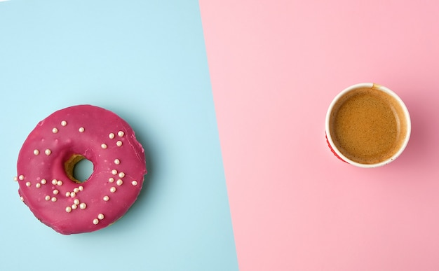 Round red glazed donut and paper cup with coffee