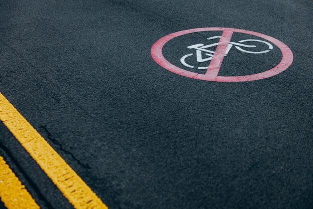 アスファルト道路に自転車の乗車禁止が印刷された丸い赤い看板。サイクリストには道がありません。人々への警告記号。