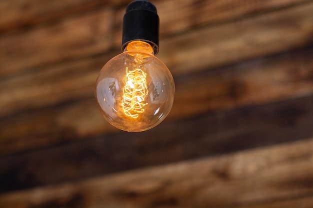 木製の背景に丸いレトロなエジソンランプ。