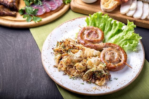 ザワークラウトの炒め物を添えた木製の串焼きの丸いローストソーセージ。ドイツ料理