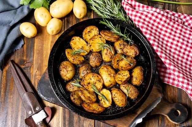 신선한 천연 허브와 함께 맛있는 구운 감자를 곁들인 둥근 구이 팬