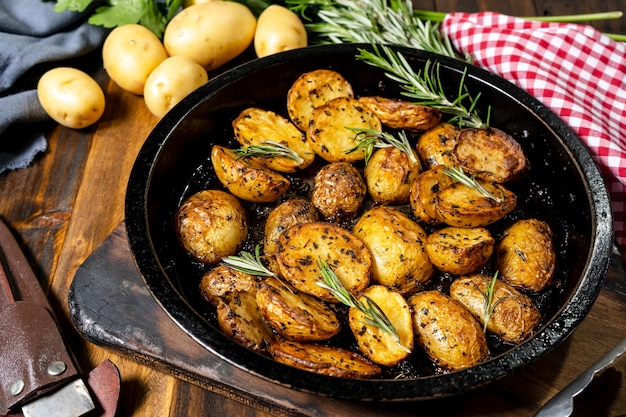 Round roasting pan with delicious roasted potatoes with fresh and natural herbs