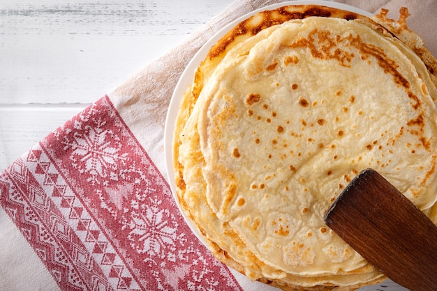 丸いロシアのパンケーキ、赤い模様のタオルにキッチンヘラ、上面図