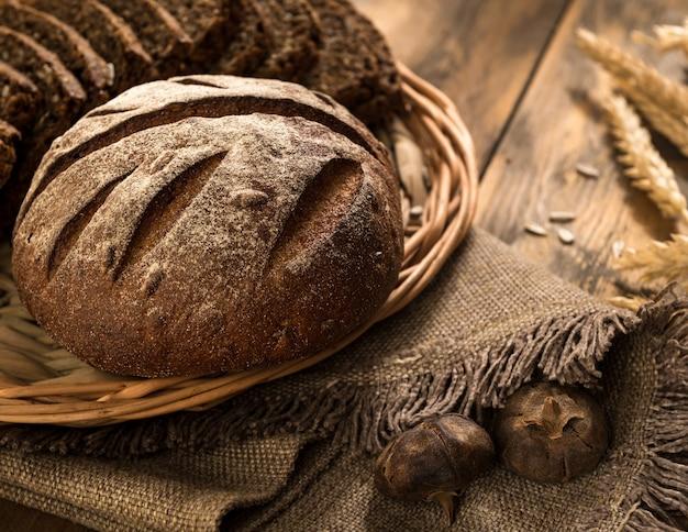 나무 표면에 냅킨과 이삭이 있는 고리버들 쟁반에 있는 둥근 호밀 빵