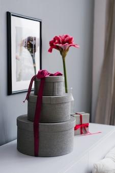자주색 리본과 아름다운 밝은 분홍색 꽃으로 묶인 둥근 성 발렌타인 선물 상자 프리미엄 사진