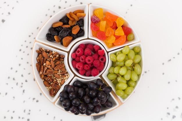 Круглый набор тарелок с орехами, малиной, сладостями, виноградом и сухофруктами на белом фоне