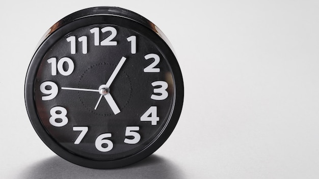 Round shape black alarm clock on gray background