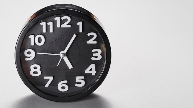 Круглый черный будильник на сером фоне