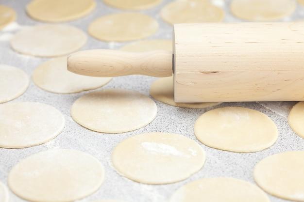 テーブルの上に小麦粉と生地と麺棒の丸型