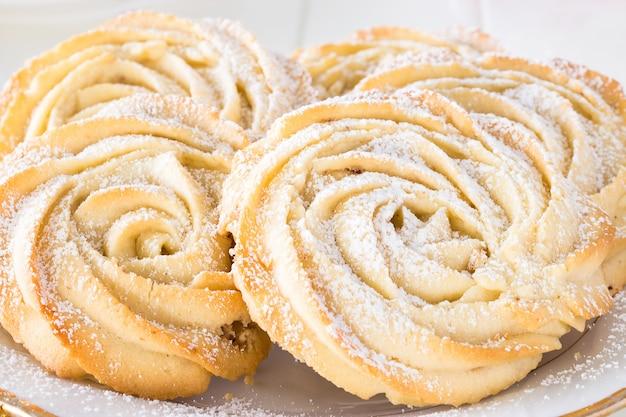Круглое песочное печенье из роз образуют тарелку белая. белый фон. скопируйте пространство. закройте вверх.