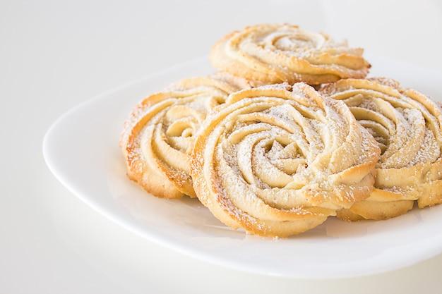 Круглое песочное печенье из роз образуют тарелку белая. белый фон. скопируйте пространство.