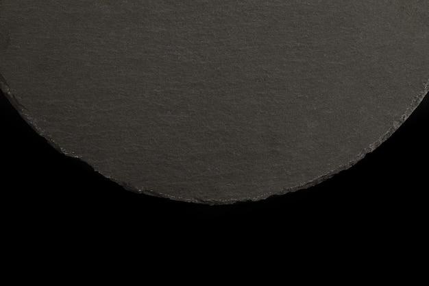 Круглая шиферная пластина на черном фоне