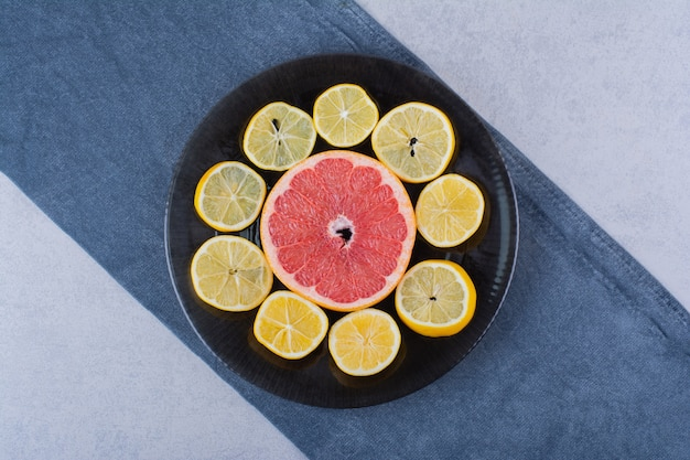 Round slices of fresh grapefruit and lemons on black plate.