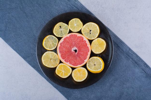 Круглые ломтики свежего грейпфрута и лимонов на черной тарелке.