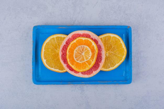 青いプレートに新鮮なグレープフルーツ、オレンジ、レモンの丸いスライス。