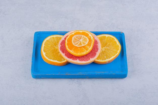 파란색 접시에 신선한 자몽, 오렌지, 레몬의 둥근 조각.