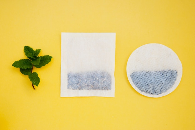 Round, square tea bags on yellow  and mint leaves, with copyspace. drinks and beverage.