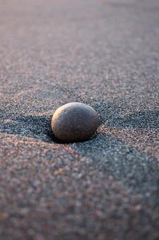 海沿いのビーチの砂の上の丸い石は、石を集めるために時間を閉じます