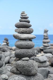丸い石が海岸にピラミッドを積み上げ、バランスの概念