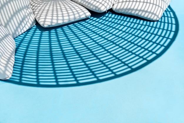 파란색 여름 휴식 의자에 둥근 줄무늬 기하학적 그림자와 흰색 베개