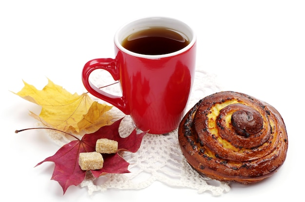Round sweet bun and cup of tea on white background