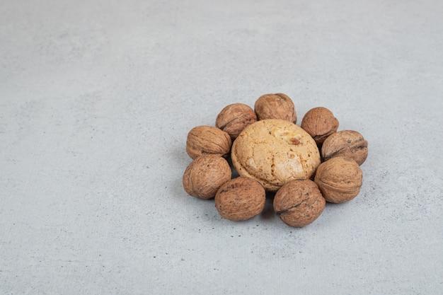 흰색 표면에 호두가 있는 둥근 달콤한 쿠키
