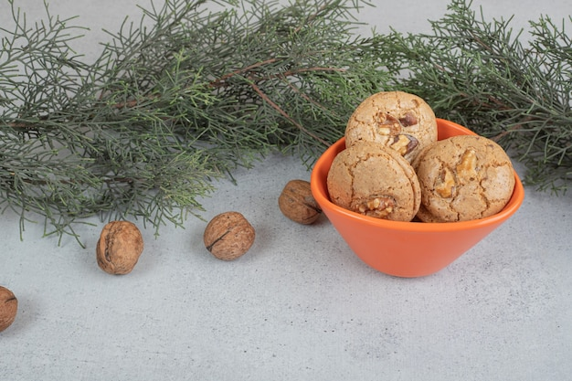Round sweet cookies with walnuts on white surface