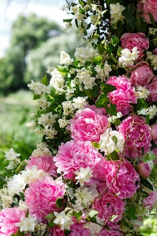 Round swing of wooden branches, decorated with a lot of peonies and roses, tulle. spring wedding floristics in white and pink tones, tender photozone