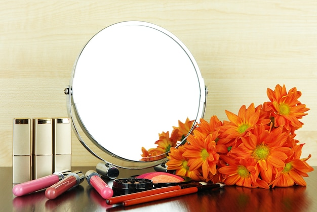 Round table mirror with cosmetics and flowers on table on wooden background