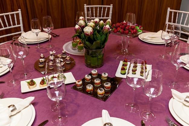 ピンクのテーブルクロスとカトラリーがセットになったラウンドテーブルには、宴会用の軽食がセットされています。ケータリング、ボンケット用サーバーテーブル