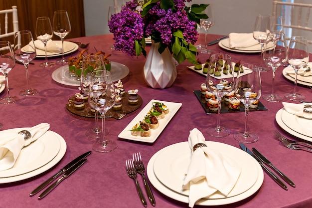연회용 간식이 포함된 분홍색 식탁보와 수저 세트가 있는 원형 테이블. 케이터링,