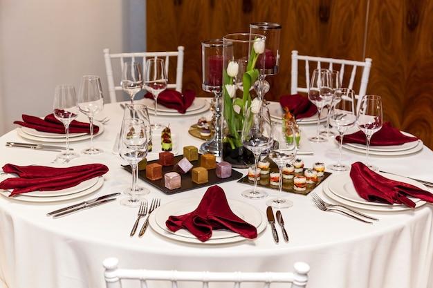 白いテーブルクロスと赤いナプキンが付いた円卓、宴会用の軽食が付いたカトラリーのセット。ケータリング、ボンケット用サーバーテーブル