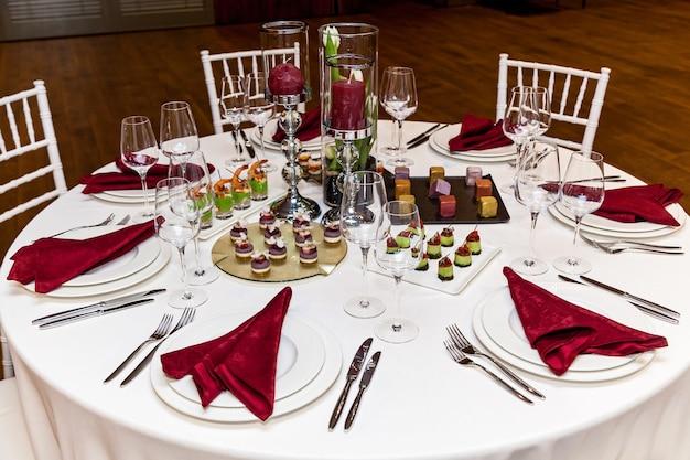 흰색 식탁보와 빨간색 냅킨이 있는 원형 테이블, 연회용 간식이 포함된 칼 붙이 세트.