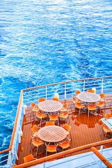 Round tables with chairs on deck of liner