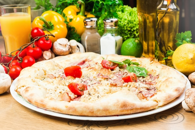 Round tasty pizza with ham and tomatoes