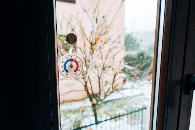 창에 둥근 온도계. 섭씨 5도. 창 밖의 눈.