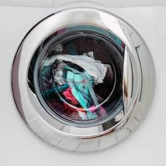Round transparent door hatch automatic washing machine, through which you can see coloured linen.