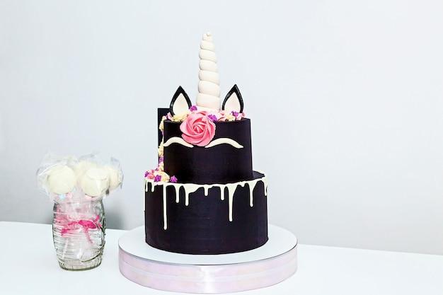 白い背景の上のユニコーンの形で丸い2層のケーキ