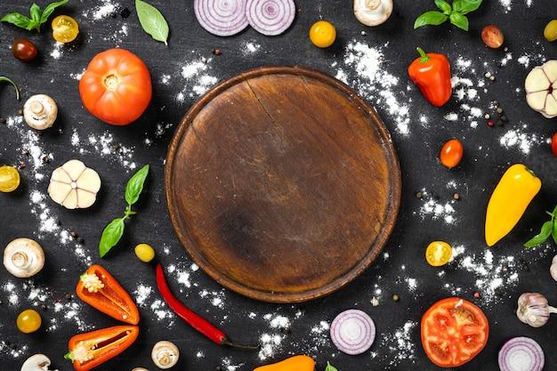 검은 돌 배경에 이탈리아 홈메이드 피자를 요리하기 위한 재료가 포함된 원형 빈티지 커팅 보드, 위쪽 전망